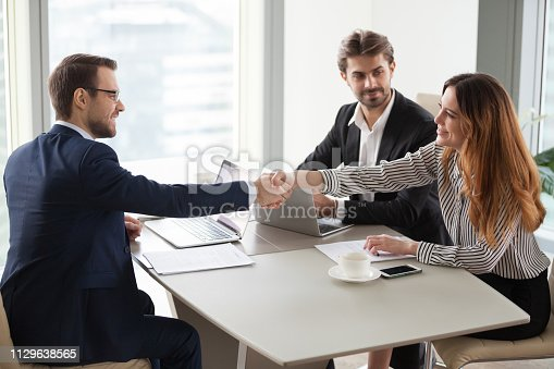 Businessman handshaking businesswoman making deal finishing group negotiations, satisfied smiling business partners conclude contract agreement shake hands expressing respect thank for group meeting