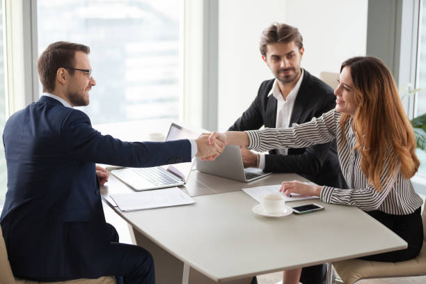 Businessman handshaking businesswoman making deal finishing group negotiations Businessman handshaking businesswoman making deal finishing group negotiations, satisfied smiling business partners conclude contract agreement shake hands expressing respect thank for group meeting seller stock pictures, royalty-free photos & images