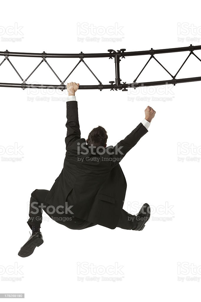Businessman hanging from a metal structure royalty-free stock photo