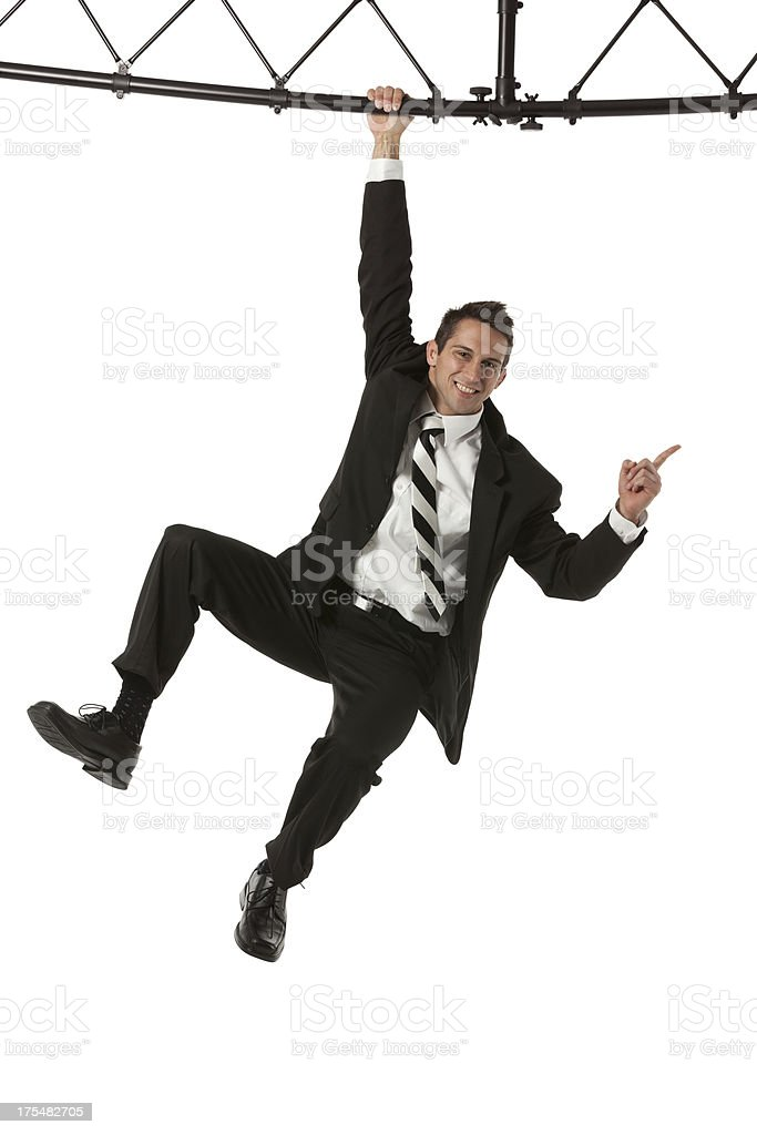 Businessman hanging from a metal structure stock photo