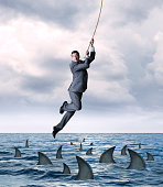 A businessman hangs on for dear life from a rope as he swings above a group of circling sharks in the ocean.  He looks down as the fear from falling into the dangerous waters grips his face.