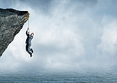 A businessman hangs on for dear life as he holds on to a rope that hangs from a cliff over a fog shrouded ocean.