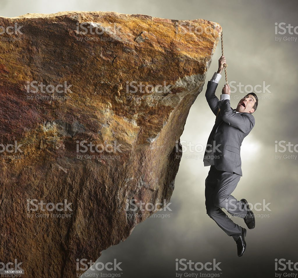 Businessman hanging from rope off of a cliff stock photo