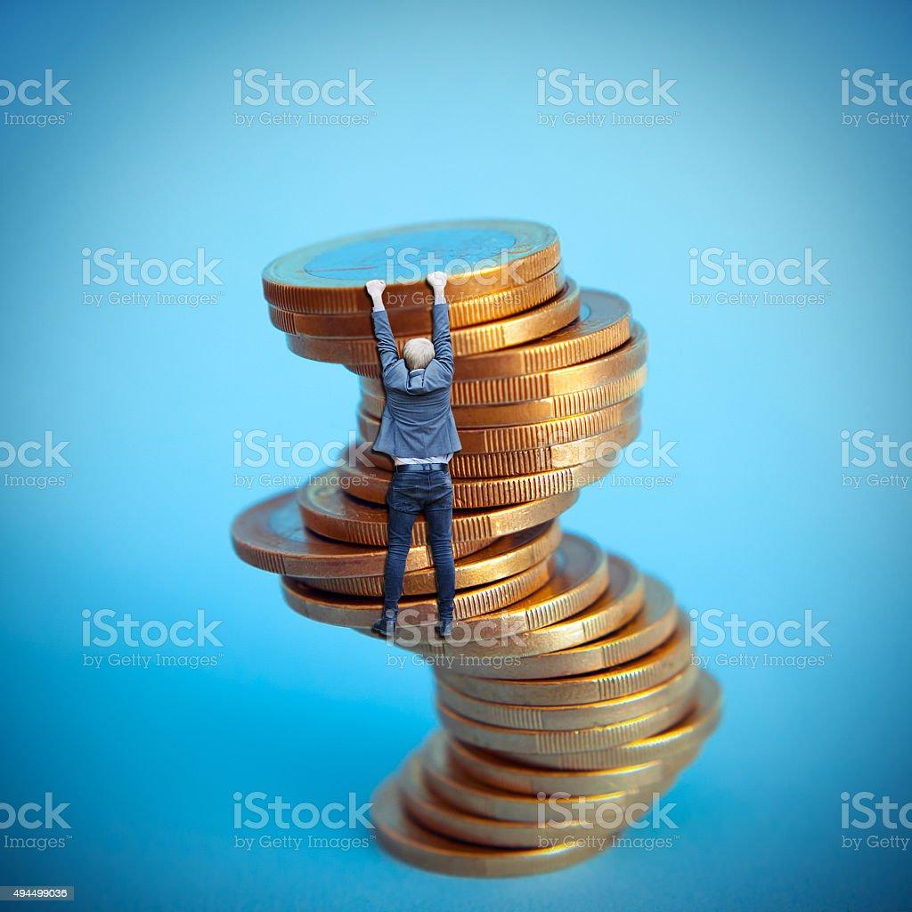businessman hanging on euro coins column stock photo