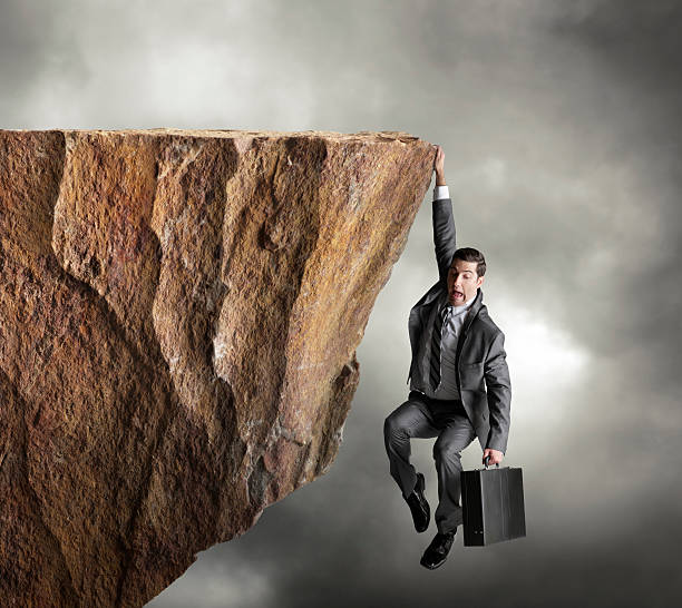 Businessman hanging on for dear life from edge of cliff stock photo