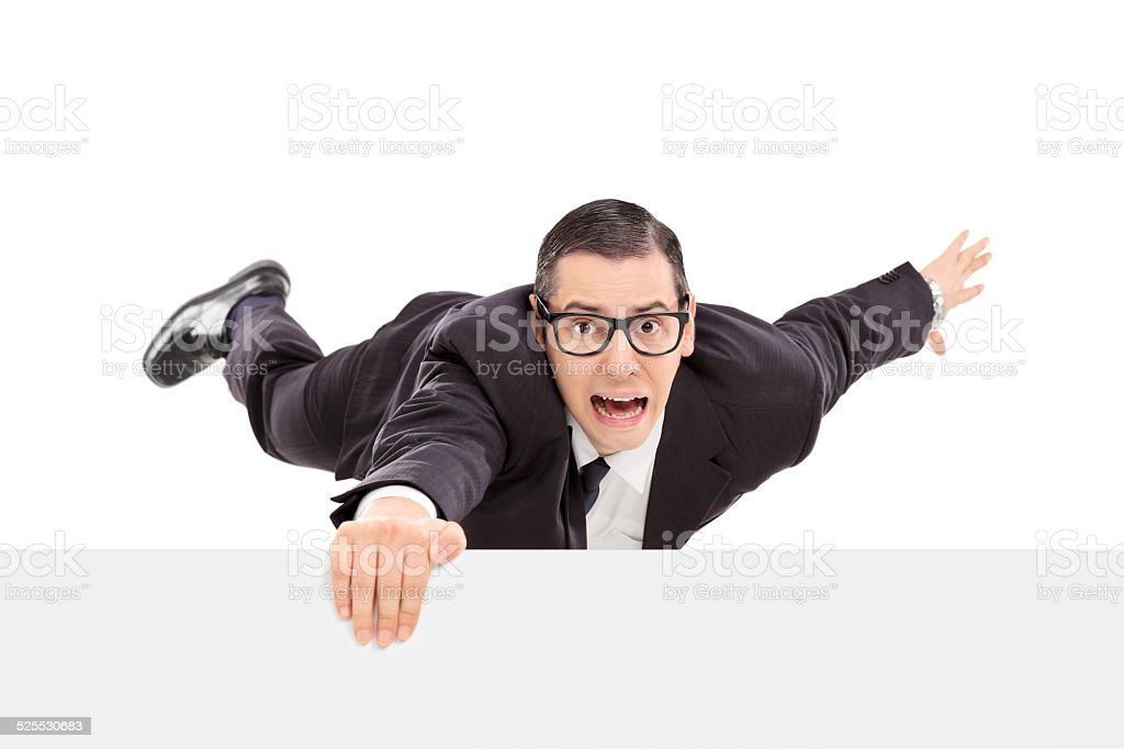 Businessman hanging on the edge of a white panel stock photo