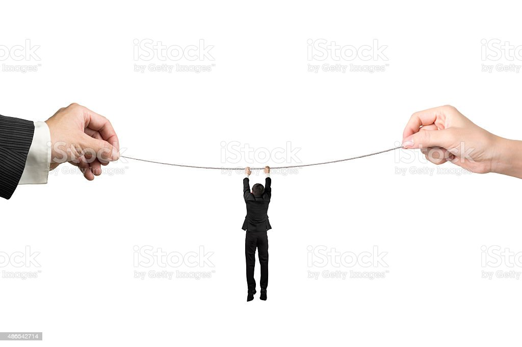 Businessman hanging on tightrope with man and woman hands holdin stock photo