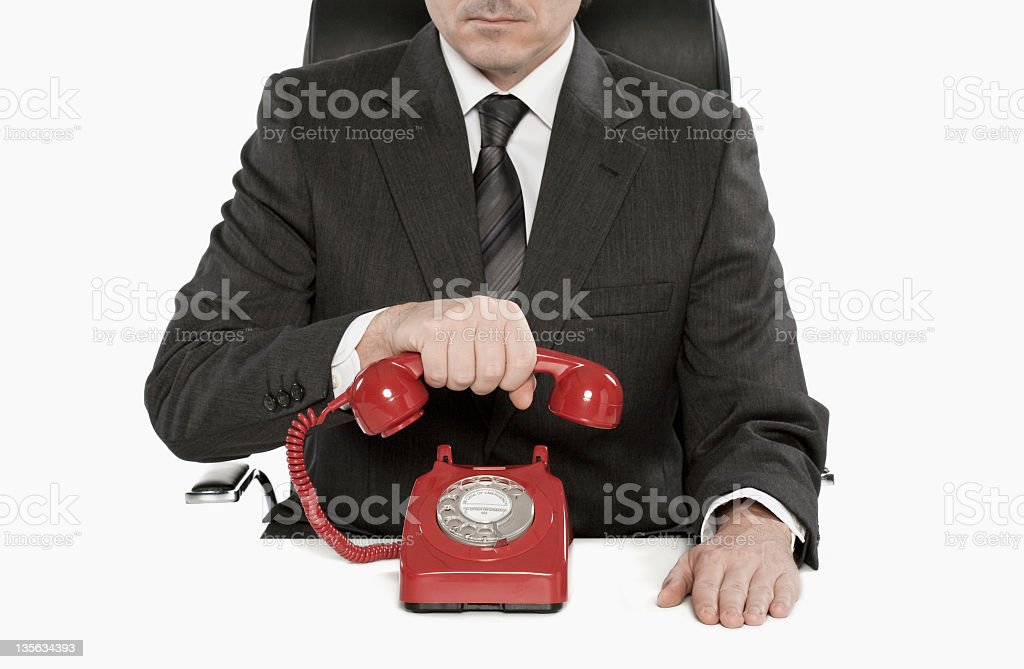 businessman hanging up red vintage telephone receiver stock photo