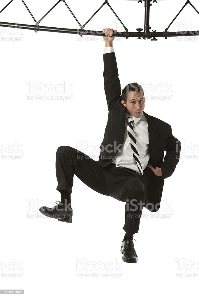Businessman hanging with a metal structure stock photo
