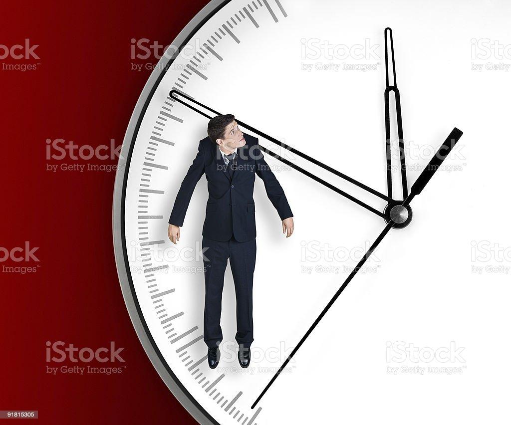 Businessman hangs on an arrow of clock. royalty-free stock photo