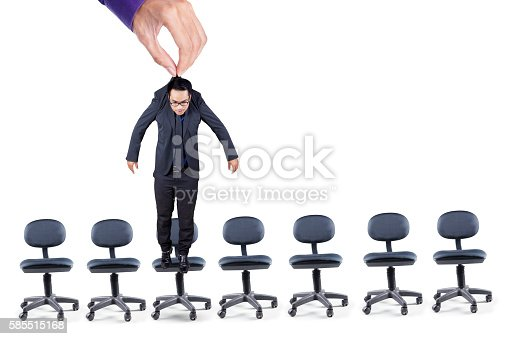 istock Businessman hangs over office chairs 585515168