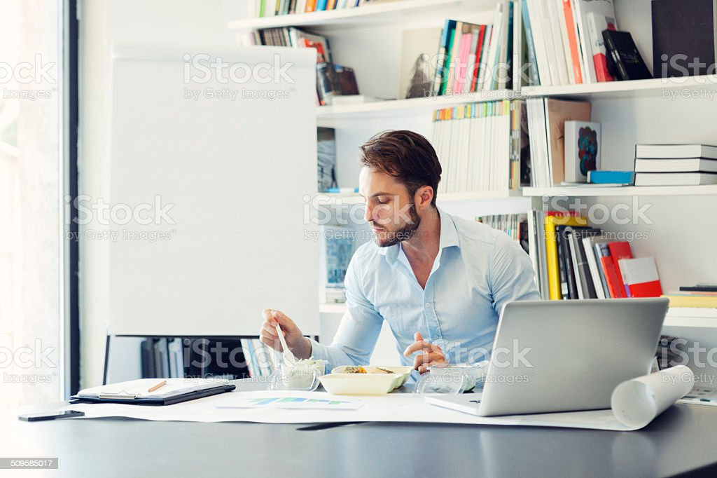 Businessman have lunch break in office. stock photo
