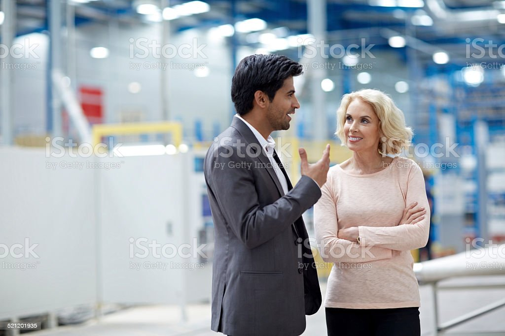 Businessman having a conversation with senior female colleague in factory stock photo