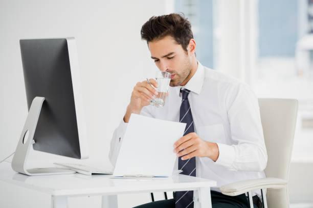 geschäftsmann mit einem glas wasser - leitungswasser trinken stock-fotos und bilder