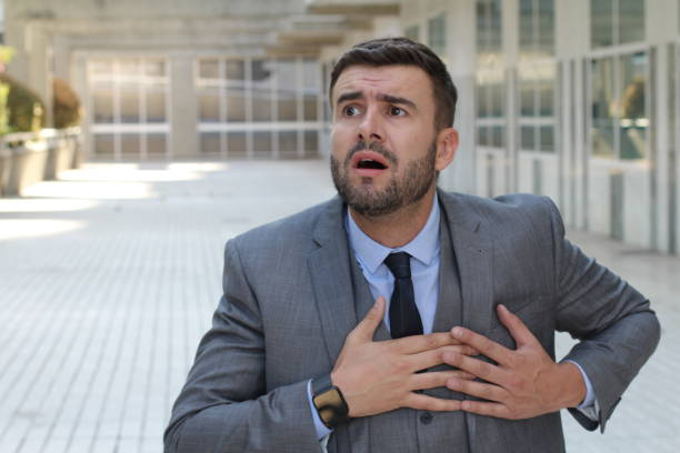 Businessman having a heart attack stock photo