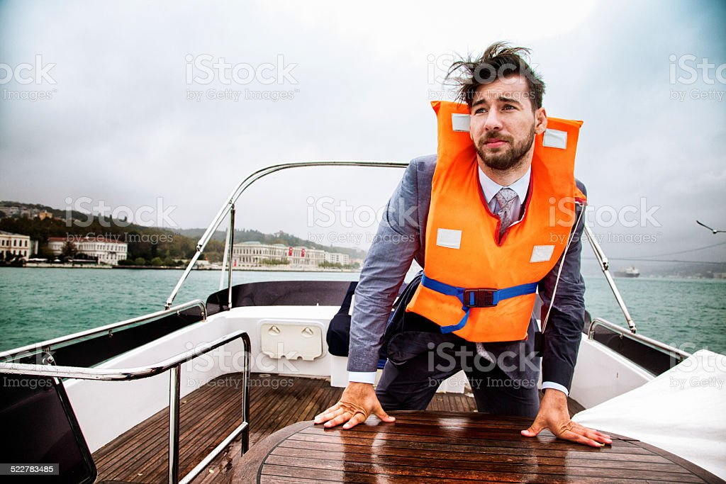 Businessman having a panic attack on his yacht in storm stock photo