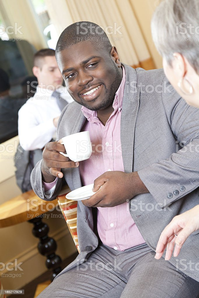Businessman having coffee in lobby with fellow associates royalty-free stock photo