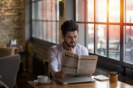 Businessman having coffee with newspaper