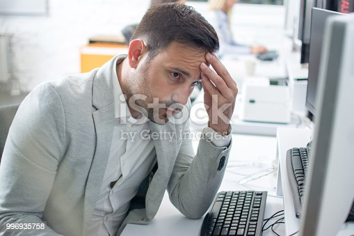 932342408istockphoto Businessman having head pain while working on computer in office 996935758
