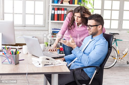 Coworkers having problems at work. Young businessman sitting on desk and working on laptop. Woman standing next to him. Both looking at laptop. As backgound tall windows and shelves with boxes and folders.