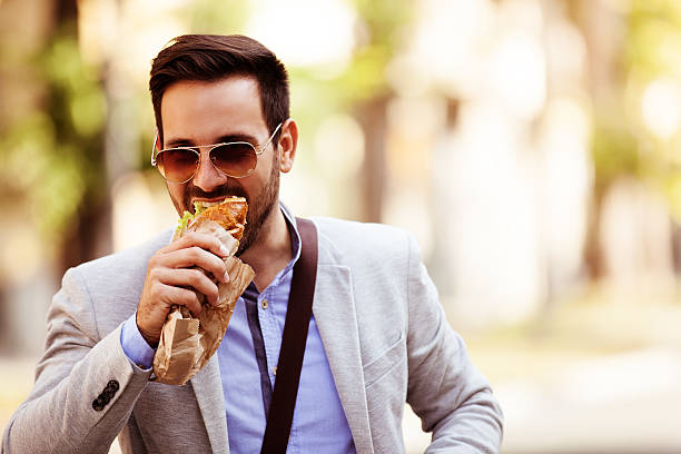 businessman having snack - on the move stock photos and pictures