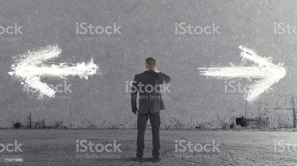Businessman having to choose between left or right royalty-free stock photo