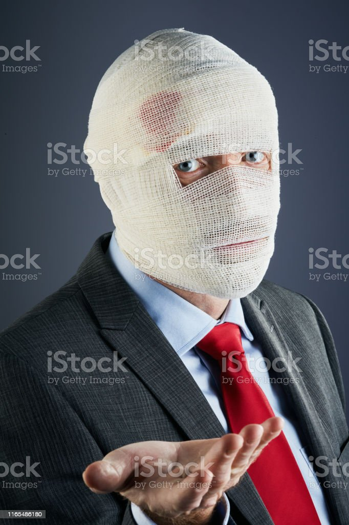 A businessman, made unrecognizable by the blood-stained bandage...