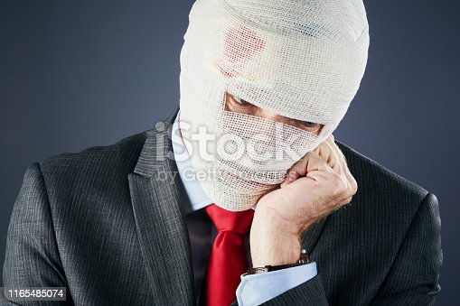 A businessman, his head completly wrapped in bloodstained bandages looks down, resting his head on his hand.
