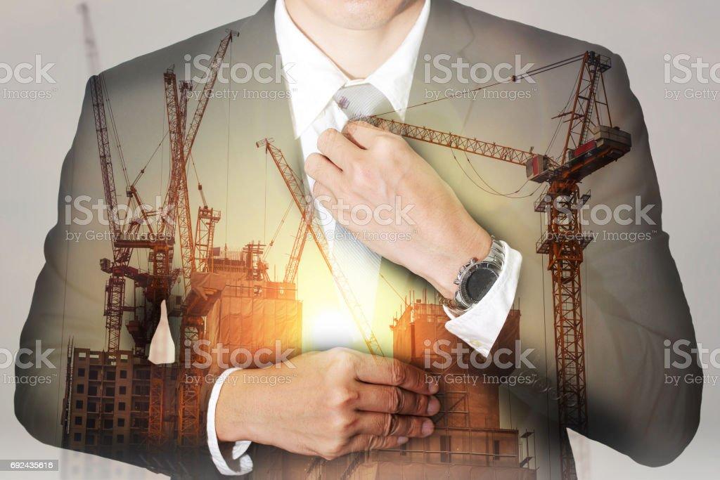 businessman held necktie dress, construction crane, bulilding and sunset stock photo