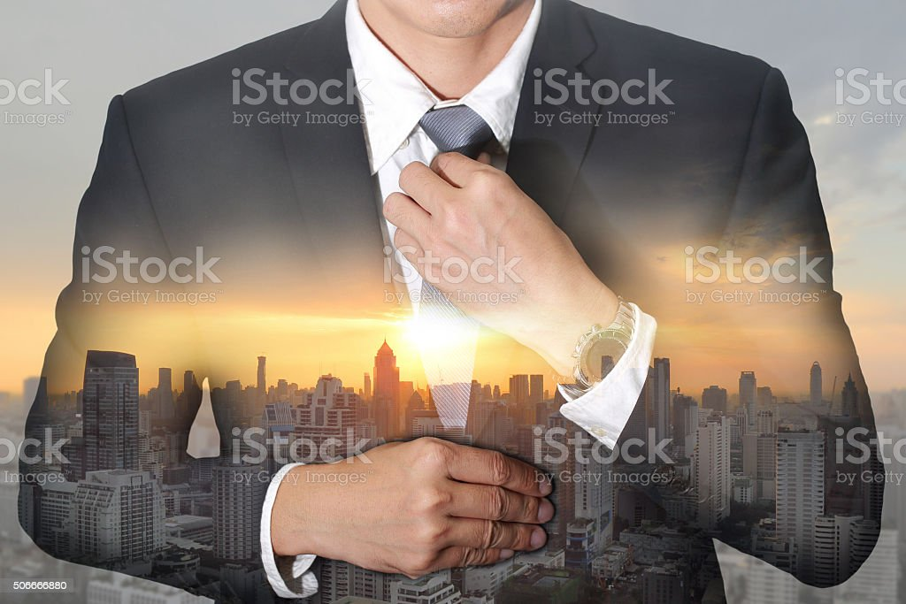 Businessman held necktie dress to look good and sunrise cityscape stock photo