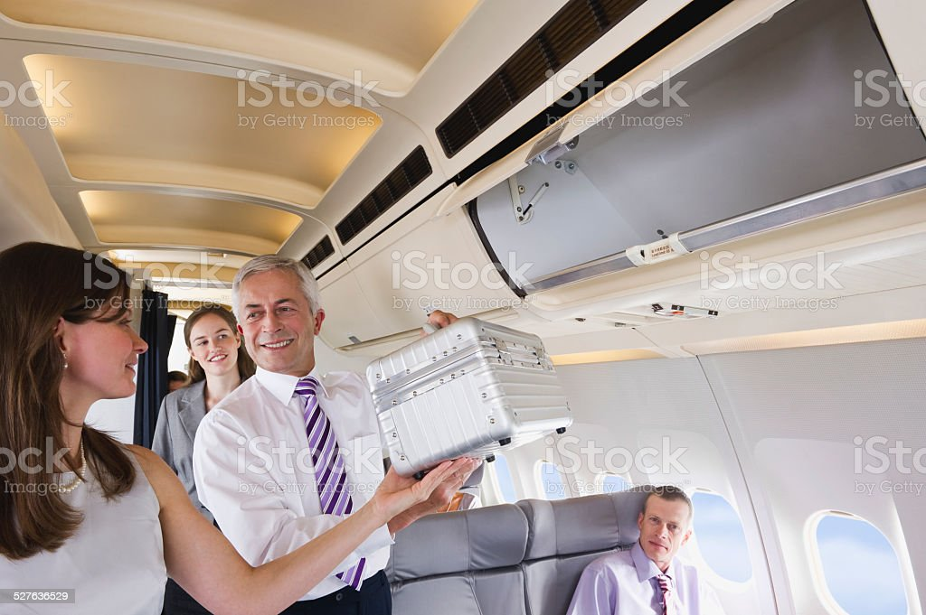 Businessman helping a businesswoman packing baggage in overhead locker stock photo