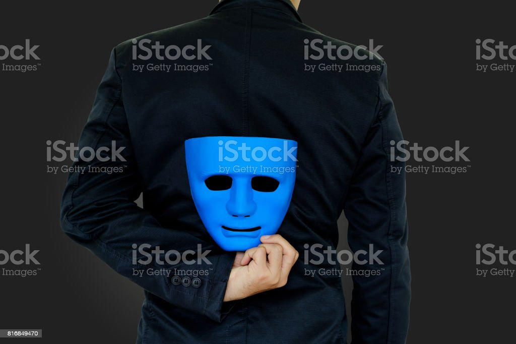 Businessman hide the mask. stock photo