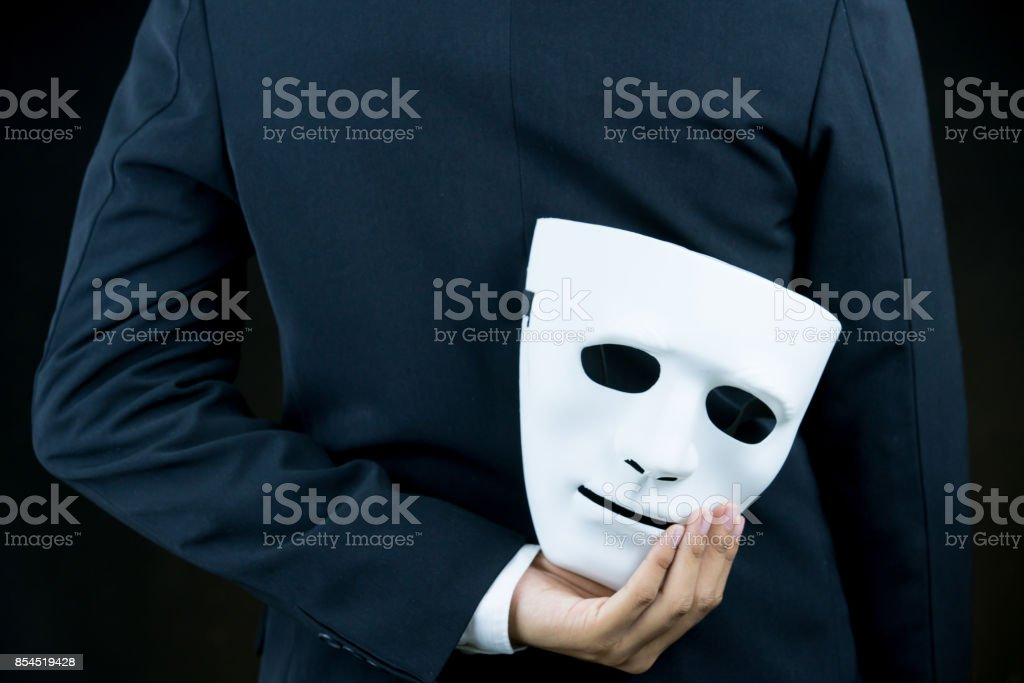 businessman hide the white mask in the hand behind his back on black background. stock photo