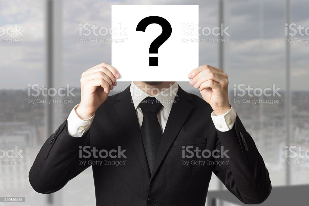 businessman hiding face behind sign question mark stock photo