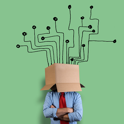 Businessman hiding his head in a cardboard box. He is in front of a circuit board hand drawn on a green wall