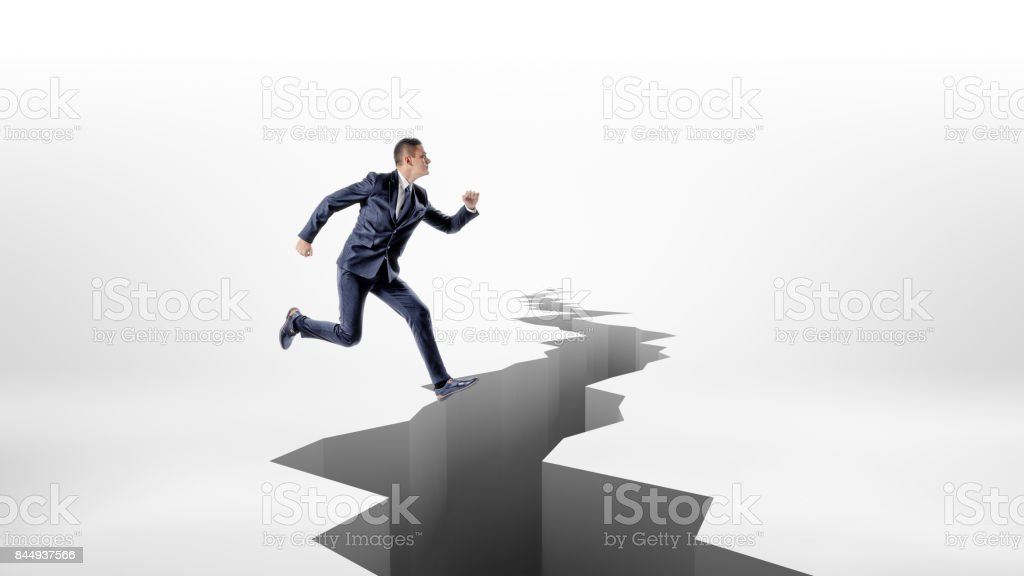 A businessman high-jumps over a long jagged earthquake rift in the ground stock photo
