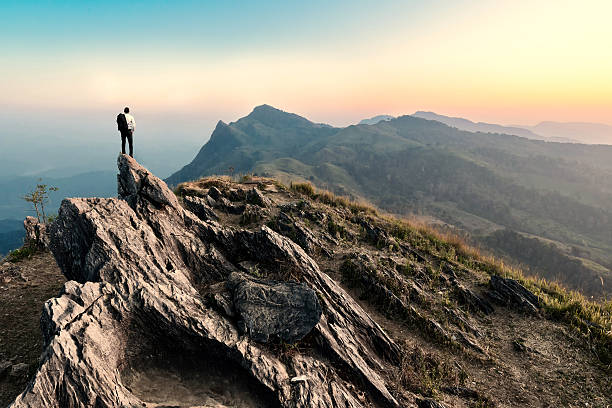 businessman hike on the peak of rocks mountain at sunset - mountain stock photos and pictures