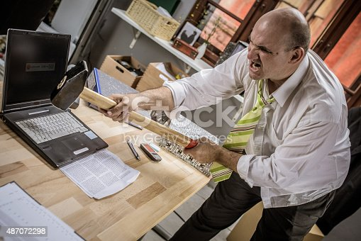593328060 istock photo Businessman hitting hammer on laptop 487072298