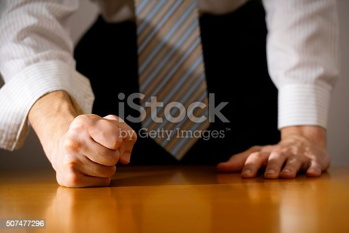 A DSLR photo of a businessman hitting the table with clenched fist. Can illustrate the concept of stress, disagreemnet, anger, etc.