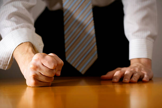 businessman hitting table with clenched fist. - aggression stock pictures, royalty-free photos & images