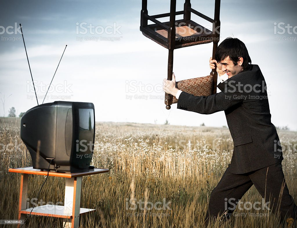 Businessman hitting the TV royalty-free stock photo