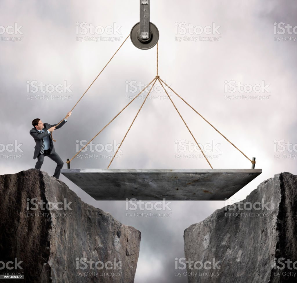 Businessman Hoists A Bridge To Bridge The Gap Between Two Cliffs stock photo