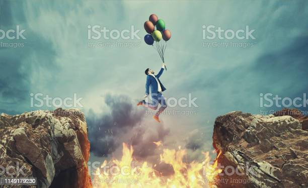 Photo of Businessman hold balloons and jumps over a fire between a gap of two mountain peaks.