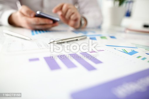istock Businessman hold smartphone aganist 1164273153