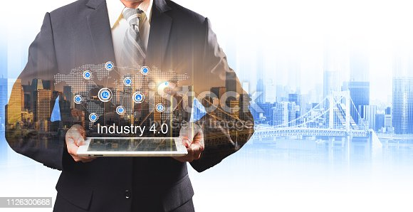 istock Businessman hold the Industry 4.0 hologram on tablet, Business and Technology, Internet of thinks and network the concept of cryptocurrency, Industry 4.0 concept