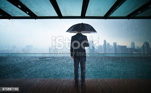 istock Businessman hold umbrella stand on rooftop ,raining day with city skyline view , risk and crisis concept . 670887150
