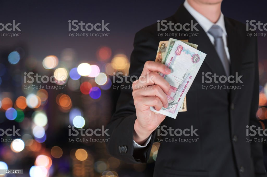 Businessman hold United Arab Emirates Dirham (AED) money on the bokeh night cityscape background as business, trade, investment and income concept stock photo