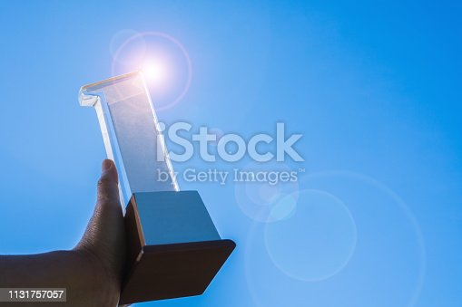 istock Businessman holding 1st award trophy Number one show first, best success achievement and prize of business as winner competition with blue sky shiny flare light background, copyspace for text 1131757057