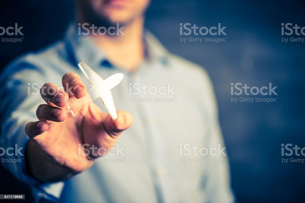 Businessman holding a airplane symbol stock photo