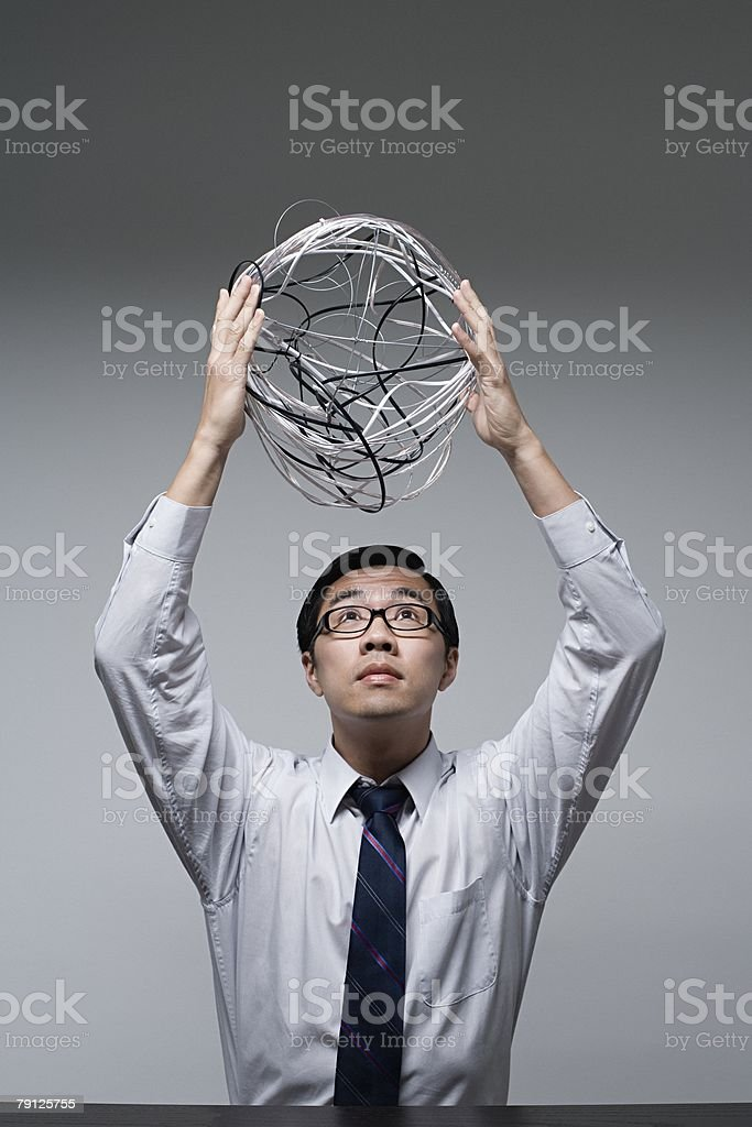 A businessman holding a ball of cables 免版稅 stock photo